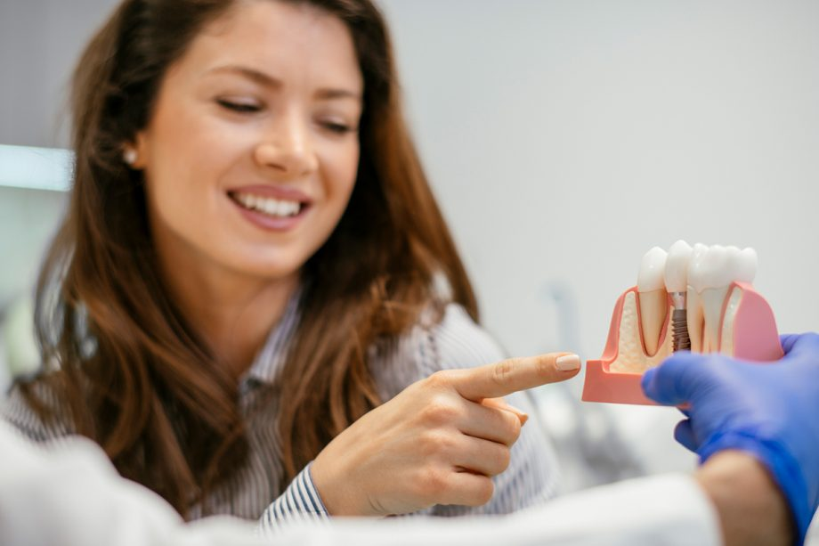 dentist holding model of dental implant, showing it to female patient