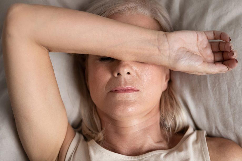 middle aged woman laying in bed with arm over face